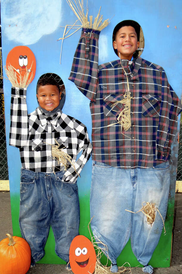 Brothers Zion and Elijah Nunez, ages 6 and 12, are scarecrow cutout attractions at Assumption Catholic School's Scarecrow Festival. Photo: Mike Lauterborn / For Hearst Connecticut Media / Fairfield Citizen