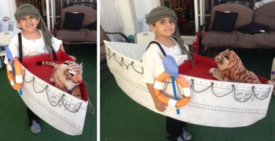 """THE LIFE OF PI (2013): Martin LaFosse says his son enjoyed the movie """"The Life of Pi,"""" which led to this outstanding costume. I was so taken by the detail work, I actually counted the little check marks and thought """"33 days at sea! Surprised the kid is still able to stand up and hold that boat."""" It's a beautiful, fun costume. Best of all: You can tell this kid is thrilled that his parents helped make the movie come to life. (But let's all agree never to tell Antoine who the orangutan is, and what really happened to her.) Photo: Courtesy Martin LaFosse"""