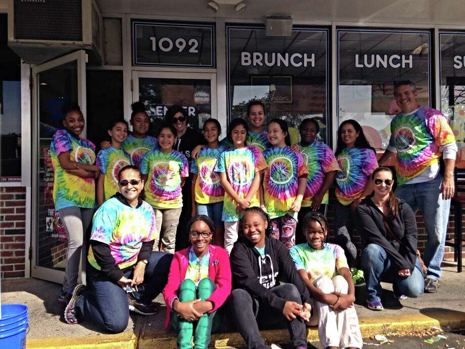 Young women from the Girls Leadership Program, a mentoring group with female city police officers, cleaned up graffiti on Stamford's West Side Saturday. Stamford police Officer Adriana Molina is seen in the foreground left, Sgt. Kelly Connelly in the rear row, Sgt. Christopher Gioelli on the far right, and to his right, Officer Leslie Lugo, dressed in one of the group's tie-dyed shirts. In front of Lugo is Officer Nicole Petrenko. Photo: Stamford Police Department / Contributed Photo / Stamford Advocate Contributed
