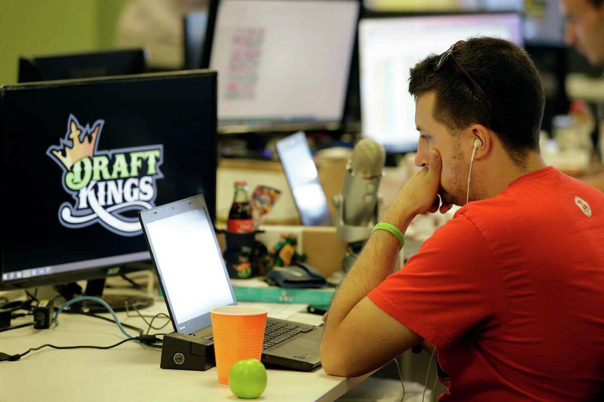 In this Sept. 9, 2015 file photo, Devlin D'Zmura, a tending news manager at DraftKings, a daily fantasy sports company, works on his laptop at the company's offices in Boston.