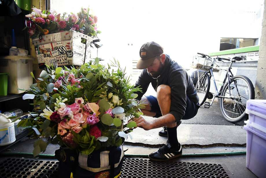 Bicycle deliveryman Joseph Lucero loads up his messenger bag and bike with bouquets at the Farmgirl Flowers stall at the San Francisco Flower Mart. Photo: Michael Short, Special To The Chronicle