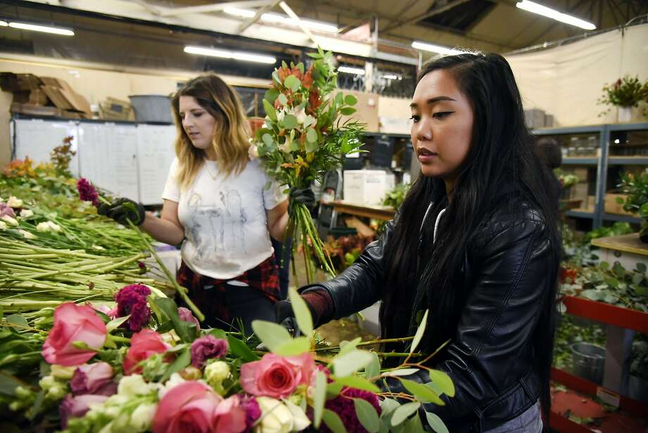 Bouquet designers Veronica Llave, right and Katie Dulka,  gather flowers as they works in the Farmgirl Flowers stall at the SF Flower Mart in San Francisco, CA Thursday, October 15, 2015. Photo: Michael Short, Special To The Chronicle