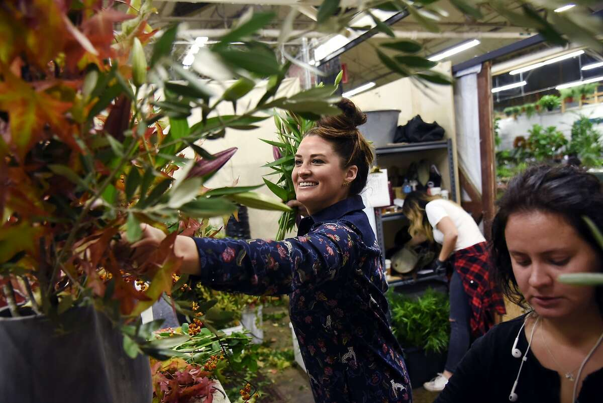 Owner and founder Christina Stembel, center, works with designer Dasha Vdovichemko as they put together an XXL size bouquet at the Farmgirl Flowers stall at the SF Flower Mart in San Francisco, CA Thursday, October 15, 2015.