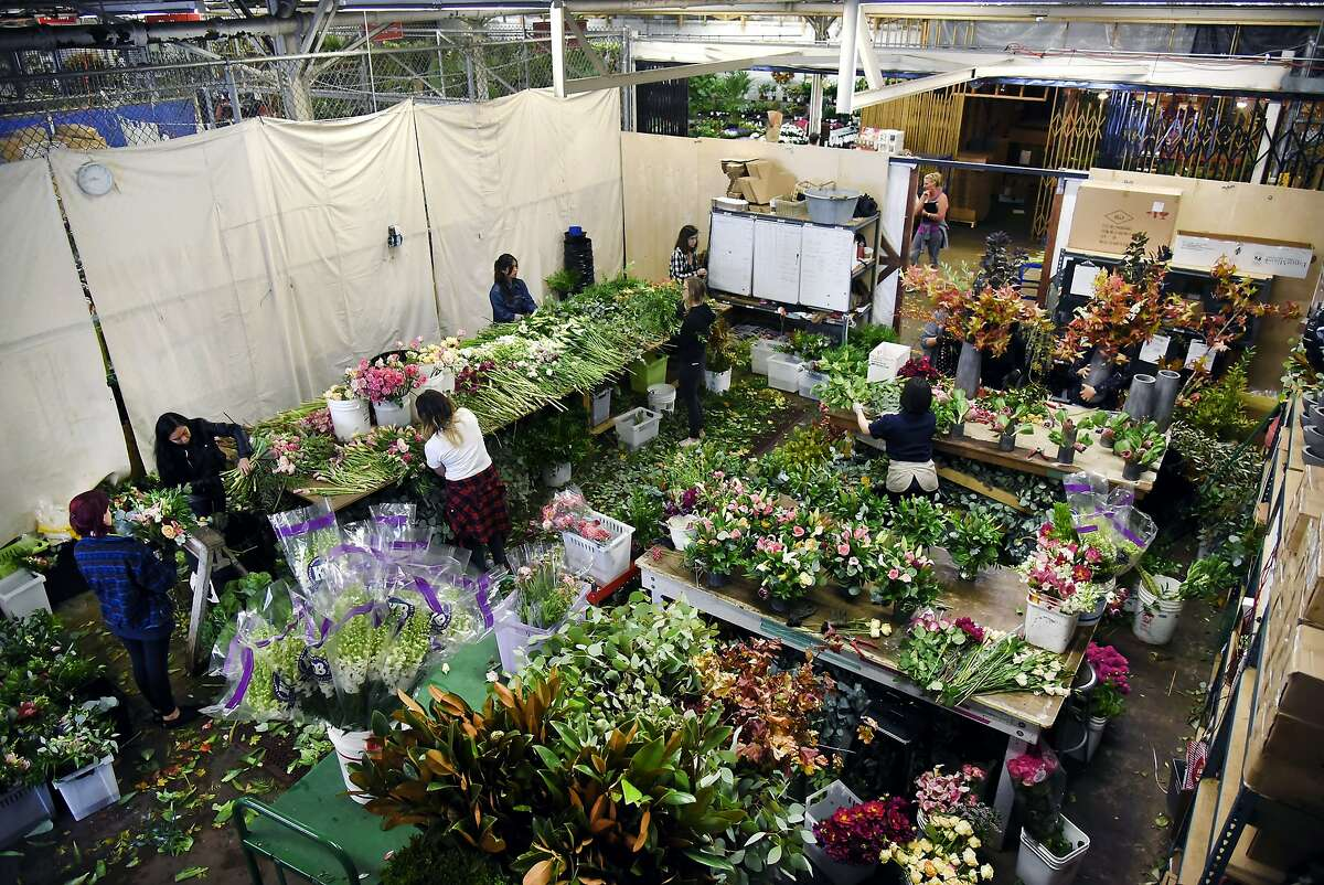 Designers work putting together the day's bouquets at the Farmgirl Flowers stall at the SF Flower Mart in San Francisco, CA Thursday, Oct. 15, 2015.