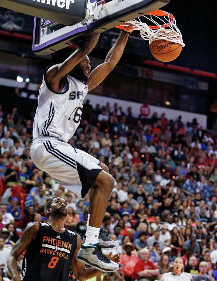 Spurs' Jonathon Simmons dunks over Phoenix Suns' Jerel McNeal during the first half of an NBA summer league basketball game on July 20, 2015, in Las Vegas. Photo: John Locher /Associated Press / AP