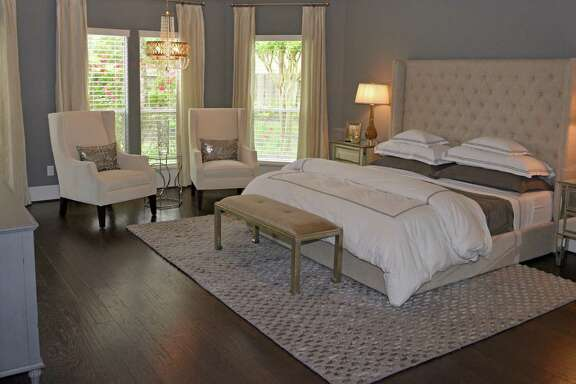 This Katy home's master bedroom, designed by Lauren Thomas, has crisp white bedding and a cushioned fabric headboard. Thomas added some gender-neutral sparkle with mirrored nightstands and metallic pillows in the chairs, and the deep gray walls and textured rug add richness.