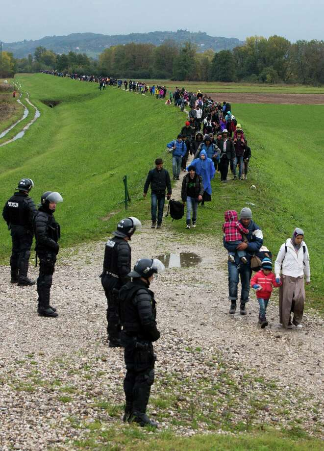 Migrants stream past Slovenian police on Monday after crossing from Croatia into Brezice, Slovenia, when authorities there lifted restrictions. Photo: Darko Bandic, STF / AP