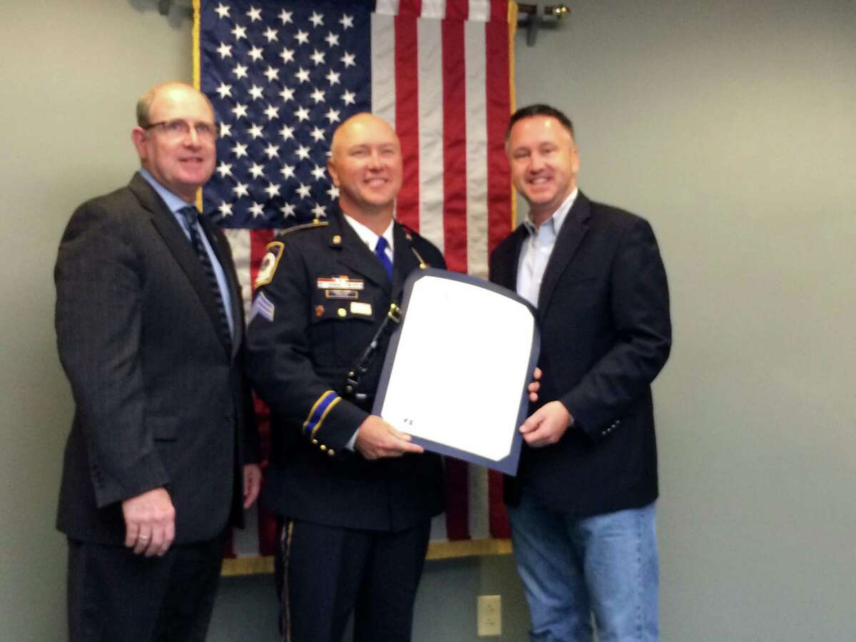 State Senators Kevin Kelly left and Rob Jane right present Seymour Police Sgt. Stephen Prajer with a certificate commending him for receiving a leadership award from Northwestern University