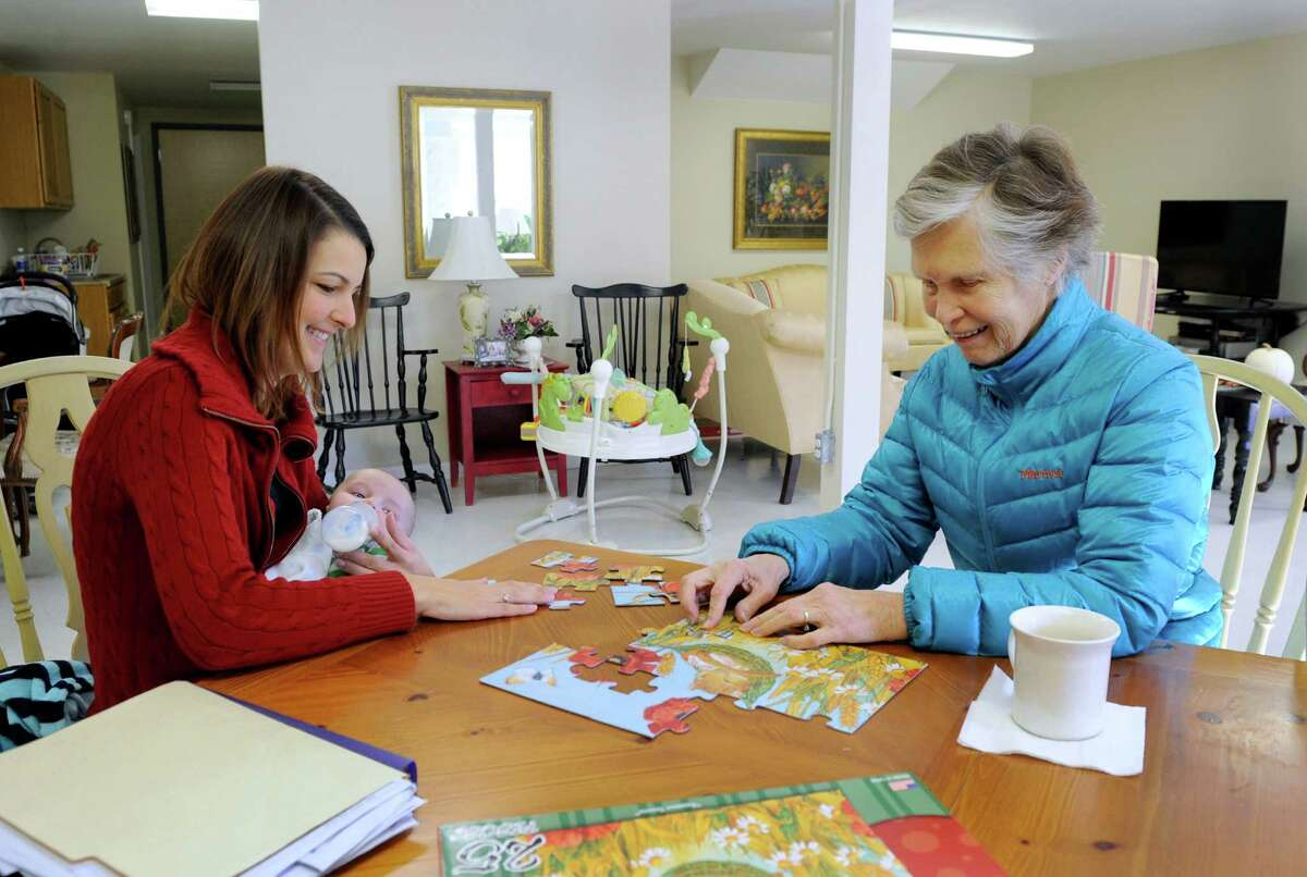 Emily Slattery, 29, left, with son Cooper Sheppard, 4 months, sits with Beth Molder, 82, of Southbury as she works on a puzzle on Monday. Slattery owns and operates Old Glory Days, an adult day care in the Sandy Hook section of Newtown.