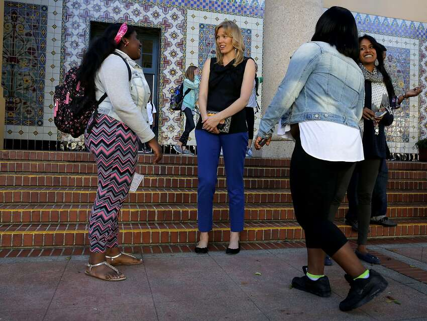 Principal Lena Van Haren (center) chats with former students Kayla Rash (left) and Honesty Williams outside Everett Middle School in San Francisco, California, on Monday, Oct. 19, 2015.