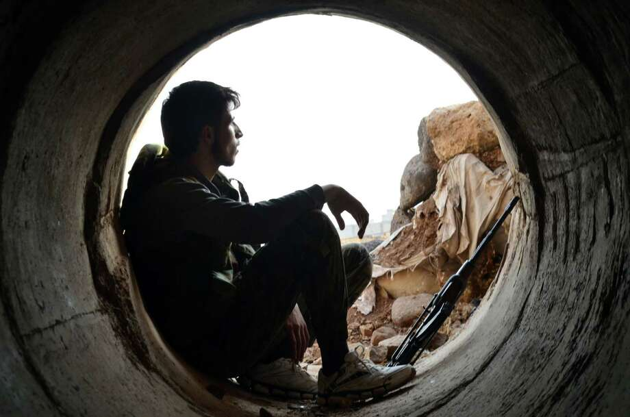 A rebel fighter rests during clashes with Russian-backed pro-government forces on the outskirts of the central Syrian province of Homs on Monday.  Photo: MAHMOUD TAHA, Stringer / AFP