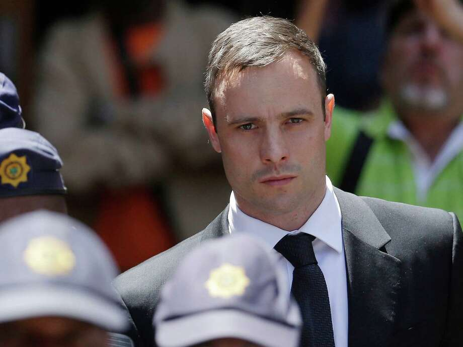 """FILE - In this Friday, Oct. 17, 2014 file photo, Oscar Pistorius is escorted by police officers as he leaves the high court in Pretoria, South Africa. A South African official says Oscar Pistorius has been released from prison and placed under house arrest. Manelisi Wolela, a spokesman for South Africa's correctional services department, said the double-amputee Olympic runner who fatally shot his girlfriend on Valentine's Day 2013 was put under """"correctional supervision"""" late on Monday, Oct. 19, 2015. (AP Photo/Themba Hadebe, File) Photo: Themba Hadebe, STF / AP"""