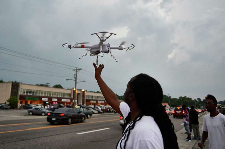 (FILES) This August 9, 2015 file photo shows a man as he operates a remote control drone camera device prior to a protest march in Ferguson, Missouri.  The United States announced October 19, 2015 that operators of drones in the United States will now have to register their remote-controlled aircraft with regulators, in an effort to limit an increasing number of dangerous flights. US Transportation Secretary Anthony Foxx and Federal Aviation Administration (FAA) head Michael Huerta said civilian-owned drones, or unmanned aerial vehicles, can cause security and privacy concerns, and aviation companies fear collisions with airplanes. AFP PHOTO / MICHAEL B. THOMASMichael B. Thomas/AFP/Getty Images Photo: MICHAEL B. THOMAS, Stringer / AFP / Getty Images / AFP