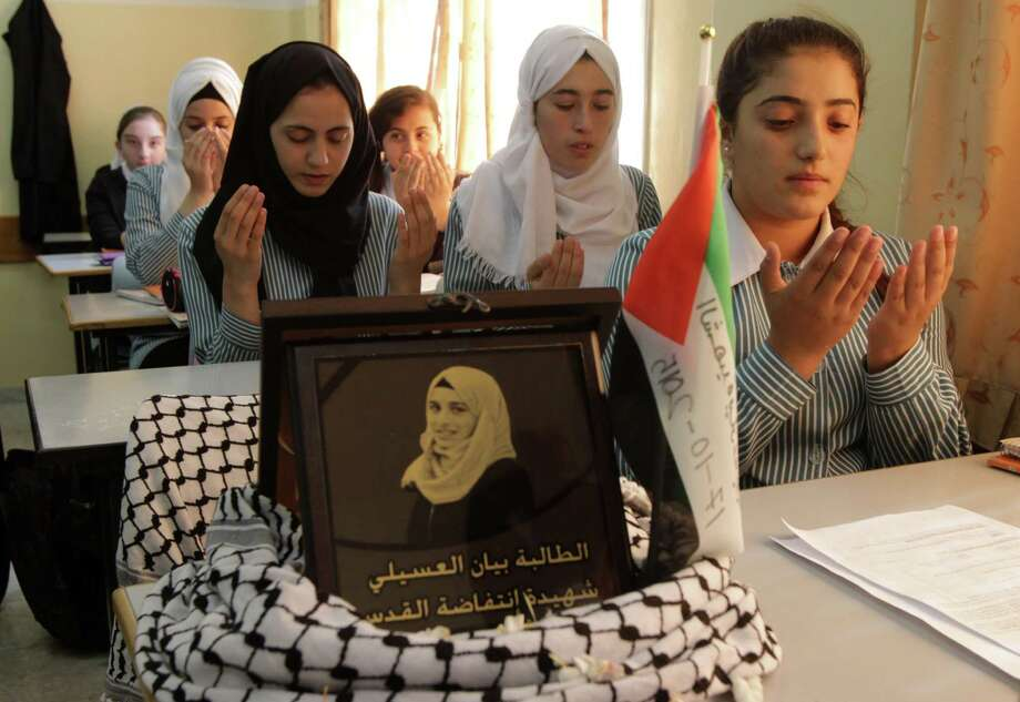 Palestinian students pray in Hebron next to a portrait of their ex-classmate, 16-year-old Bayan al-Osaily, who was killed by a soldier in the recent surge of violence. Photo: HAZEM BADER, Stringer / AFP