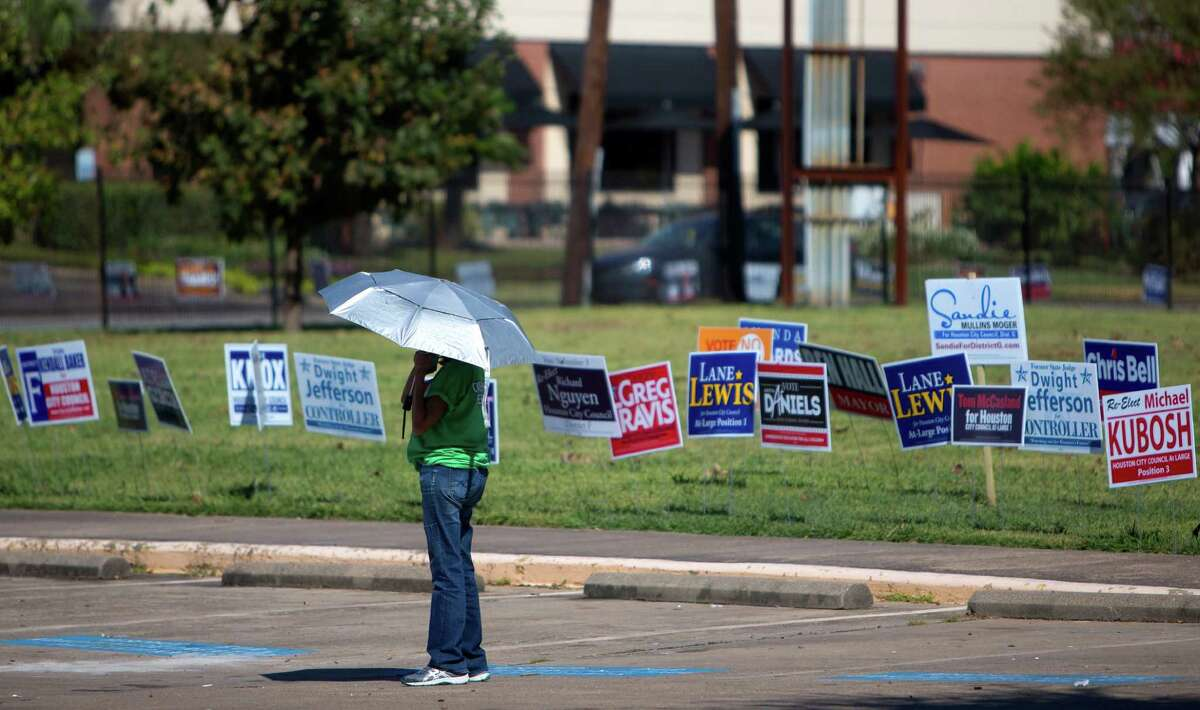 Chris Carmona stands amongst candidate signs as she hands out fliers to voters at the Metropolitan Multi-Services Center, Monday, Oct. 19, 2015, in Houston.