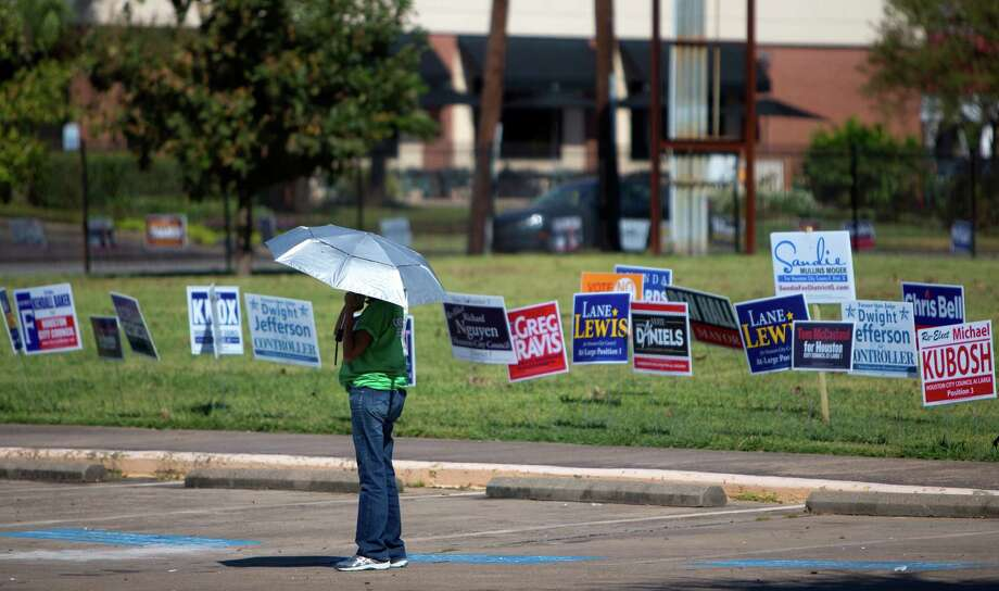 Chris Carmona stands amongst candidate signs as she hands out fliers to voters at the Metropolitan Multi-Services Center, Monday, Oct. 19, 2015, in Houston. Photo: Cody Duty, Houston Chronicle / © 2015 Houston Chronicle