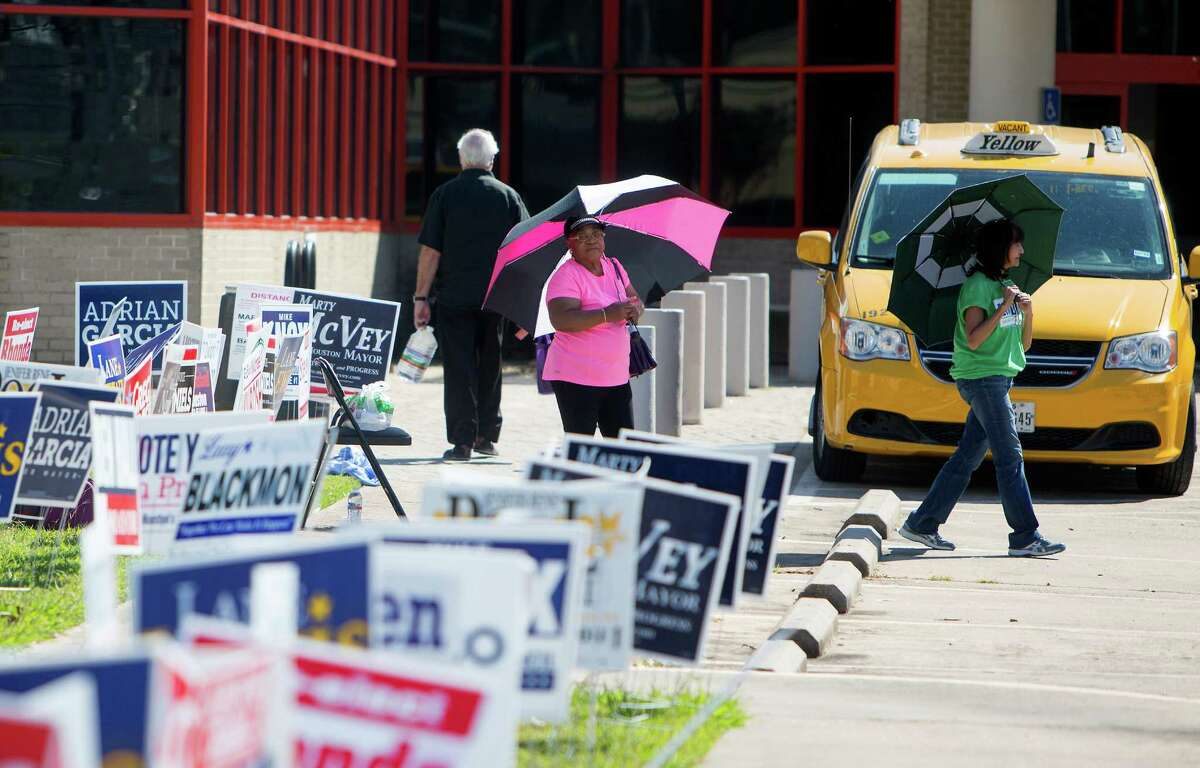 Leatrix Lamberson, left, and Chris Carmona, right, stand amongst candidate signs as they hand out fliers to voters at the Metropolitan Multi-Services Center, Monday, Oct. 19, 2015, in Houston.