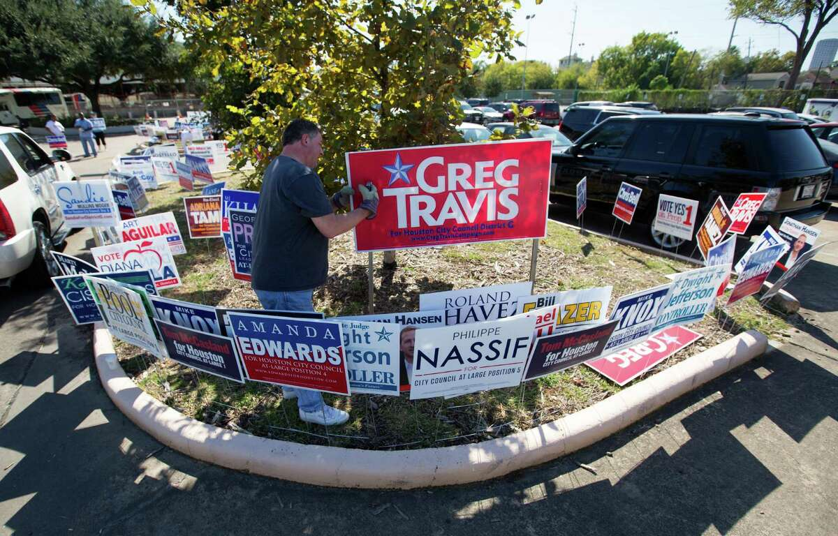 Greg Travis puts up a sign for his campaign at the Metropolitan Multi-Services Center, Monday, Oct. 19, 2015, in Houston.