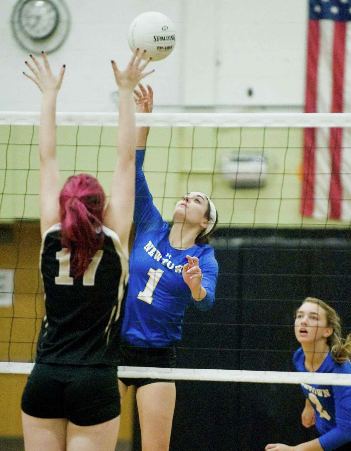Newtown High School's Jamie Calandro tipping the ball over the net in a game against Joel Barlow High School, played at Barlow. Monday, Oct. 19, 2015