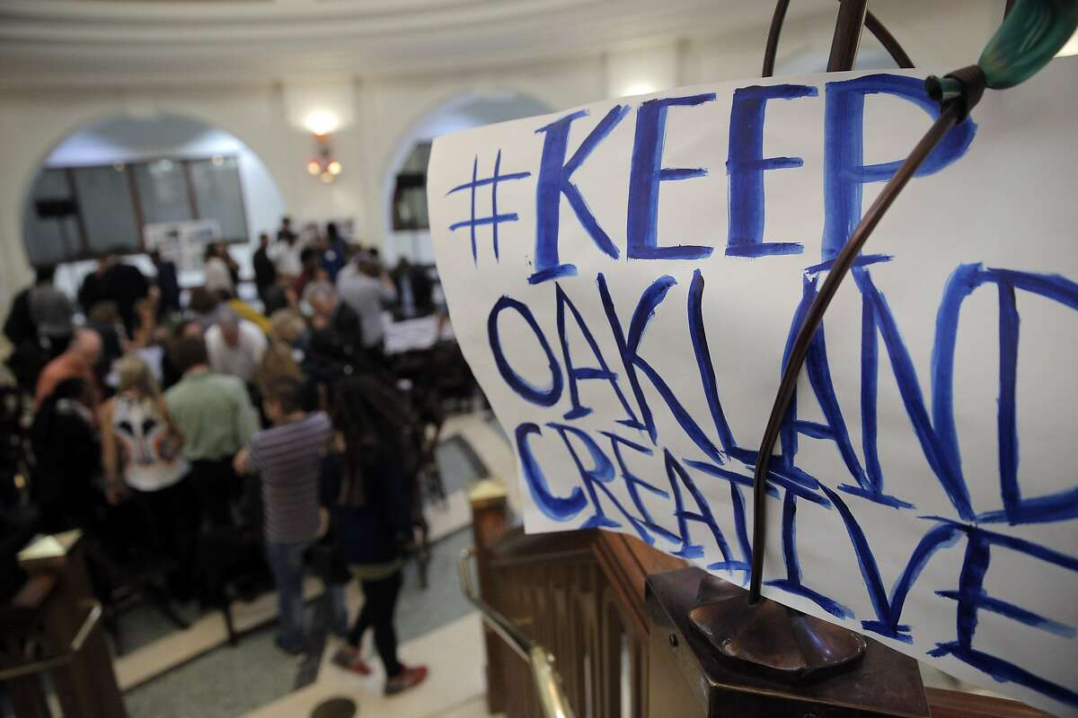 A sign from a rally organized by Oakland's Creative Neighborhood Coalition to defend Oakland's culture hangs above a meeting the city of Oakalnd organized to help redesign downtown Oakland Monday night. The rally preceded the meeting in Oakland, Calif., on Monday, October 19, 2015.