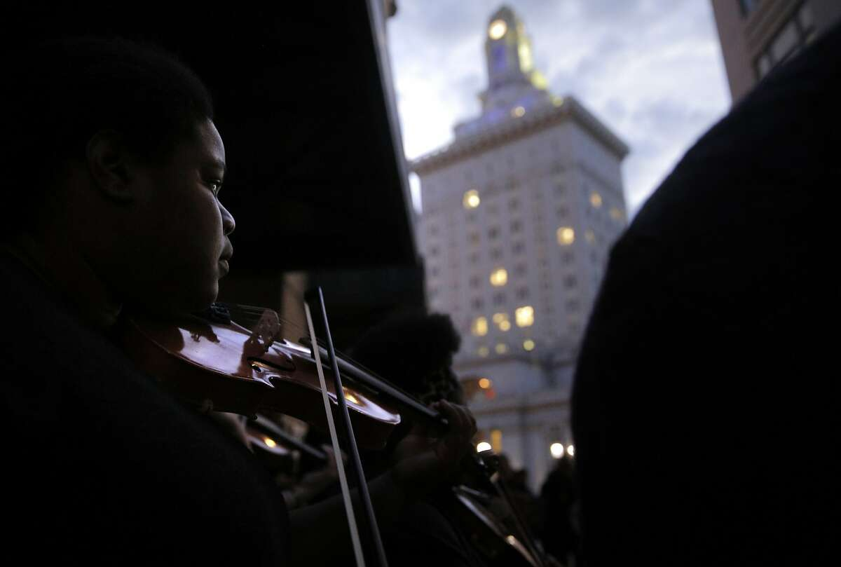 Emma Price of the Oakland Creative Voices plays during a rally organized by Oakland's Creative Neighborhood Coalition to defend Oakland's culture on Monday night. The rally preceded a meeting the city held to redesign downtown in Oakland, Calif., on Monday, October 19, 2015.