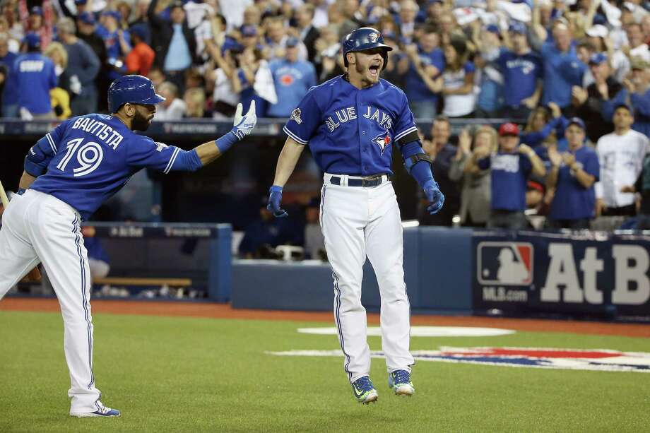 Blue Jays slugger Josh Donaldson, right, can't keep his feet on the ground while celebrating with teammate Jose Bautista after hitting a two-run homer in the third inning of Monday night's game against the Royals. Photo: Tom Szczerbowski, Stringer / 2015 Getty Images