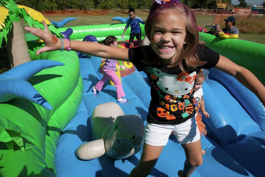 Madison Carrion, 7, enjoys one of the several inflatable play areas at the annual Bridgeland Howl-O-Ween Fest. Photo: Bridgeland / John Everett Photography
