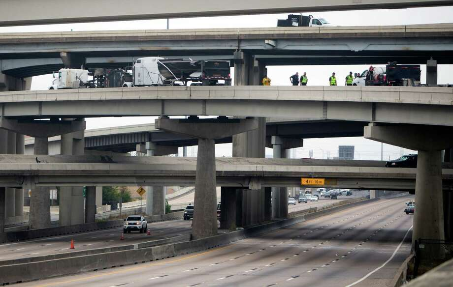 Authorities clean up a wreck on U.S. 59 at the West Loop northbound, Tuesday, Oct. 20, 2015, in Houston. All southbound traffic on U.S. 59 was diverted to the West Loop northbound after a dump truck overturned on an on ramp, dumping debris onto the highway below. According to Houston TranStar, the truck overturned on the ramp from U.S. 59 onto the West Loop southbound, spilling chunks of cement in its bed over the ramp and onto the highway. Photo: Cody Duty, Houston Chronicle / © 2015 Houston Chronicle