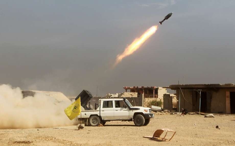 Iraqi Shiite fighters from the Popular Mobilisation units, fighting alongside Iraqi government forces, fire a rocket during a military operation against Islamic State (IS) group jihadists as they advance towards the centre of Baiji, some 200 kilometres north of Baghdad on October 19, 2015. Iraqi forces advanced on three fronts against the Islamic State group, flushing out pockets of resistance in and around Baiji and closing in on Ramadi and Hawijah, officers said. Photo: Ahmad Al-rubaye, AFP / Getty Images
