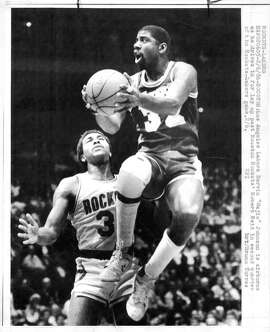 "ROCKETS-LAKERS 2/6/86 - HOUSTON:  Los Angeles Lakers Earvin ""Magic"" Johnson is airborne as he drives in for lay up past Houston Rockets' Robert Reid in second quarter of the Rockets-Lakers game, 2/6. UPI  brt / Bruno Torres  Ran: Feb 7 1986, 6*..  p. 88"