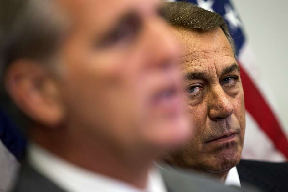 Former House Speaker John Boehner of Ohio listens at right as House Majority Leader Kevin McCarthy of Calif., speaks during a new conference on Capitol Hill in Washington. Boehner wants out. He really does. But the Ohio House Republican is staying put, for now — and that could improve the chances for a debt limit increase by early next month to avoid a market-shattering government default and possibly a bipartisan budget deal to head off a government shutdown in December. Conservative hardliners have already forced Boehner to announce he's leaving and then caused further chaos by blocking the ascension of McCarthy. Photo: Evan Vucci, Associated Press