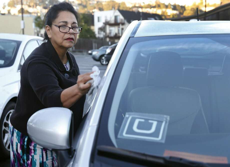 Blanca Whitehead cleans the exterior of her car before picking up passengers requesting rides using the UberPool service option in San Francisco, Calif. on Tuesday, Oct. 20, 2015. Uber is encouraging riders using the service to ask employees to subsidize their daily commutes. Photo: Paul Chinn, The Chronicle