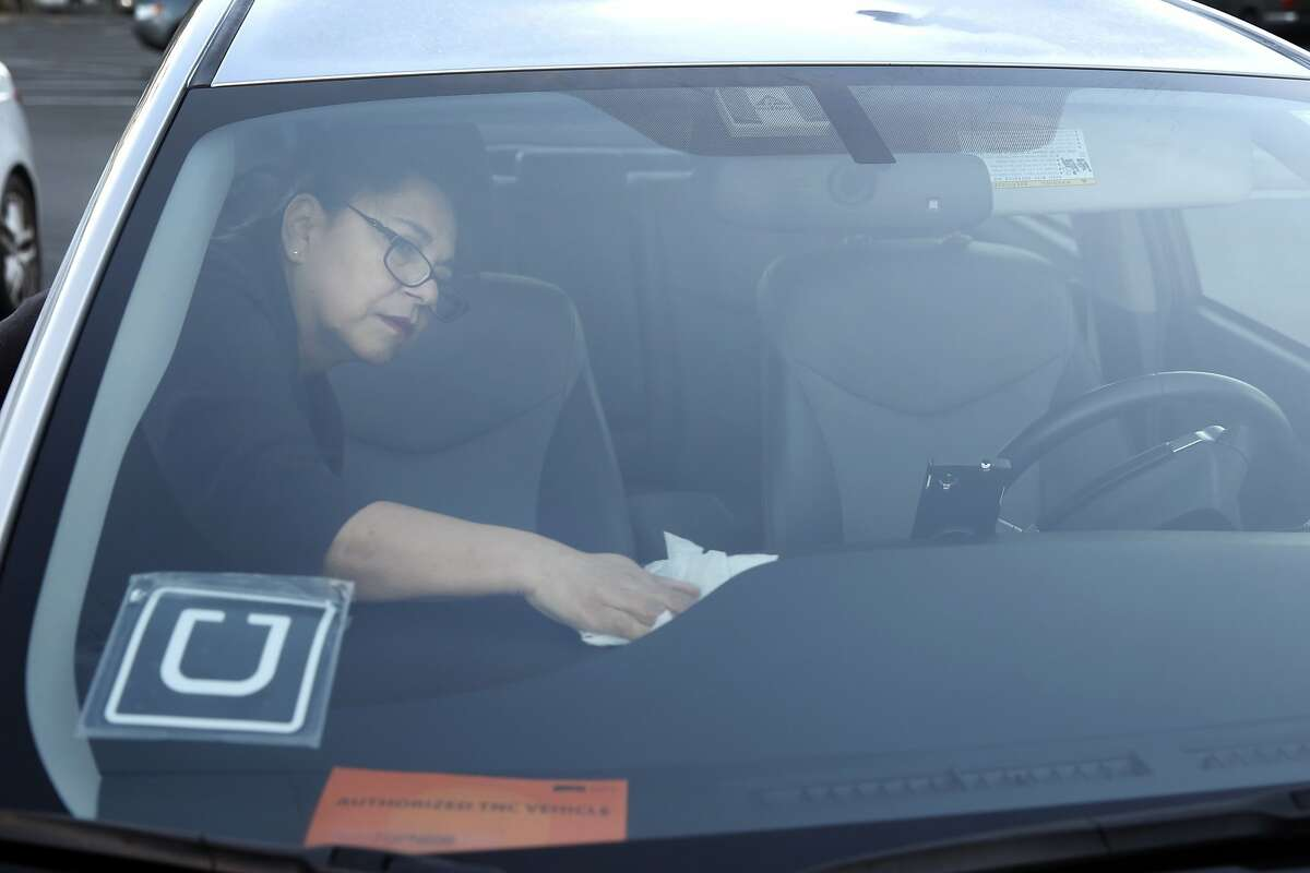 Blanca Whitehead cleans the exterior of her car before picking up passengers requesting rides using the UberPool service option in San Francisco, Calif. on Tuesday, Oct. 20, 2015. Uber is encouraging riders using the service to ask employees to subsidize their daily commutes.