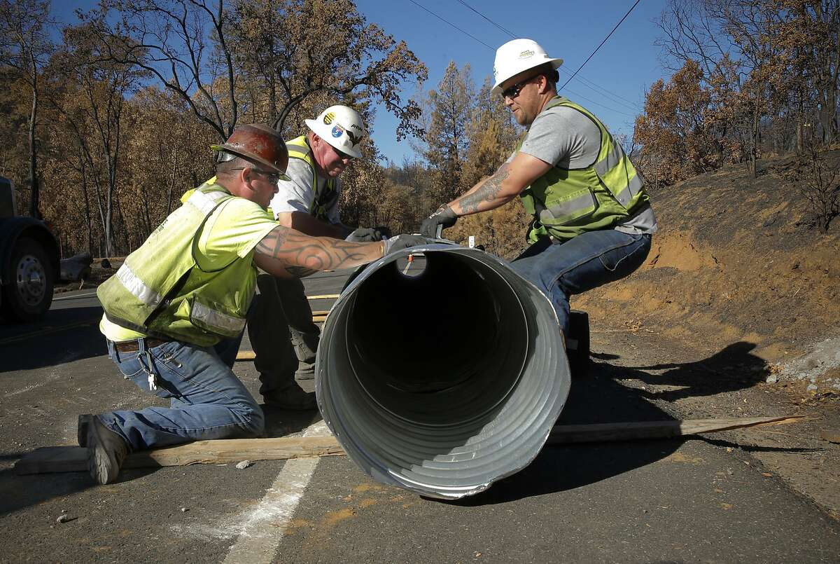 Caltrans contractors Gordon Davis, Russ Potter and Greg Neely, work to replace a fire damaged drainage pipe that runs under highway 175, on Tues. Oct. 20, 2015, in preparation of possible heavy rains this winter after the Valley Fire swept through highway near Middletown, Calif.