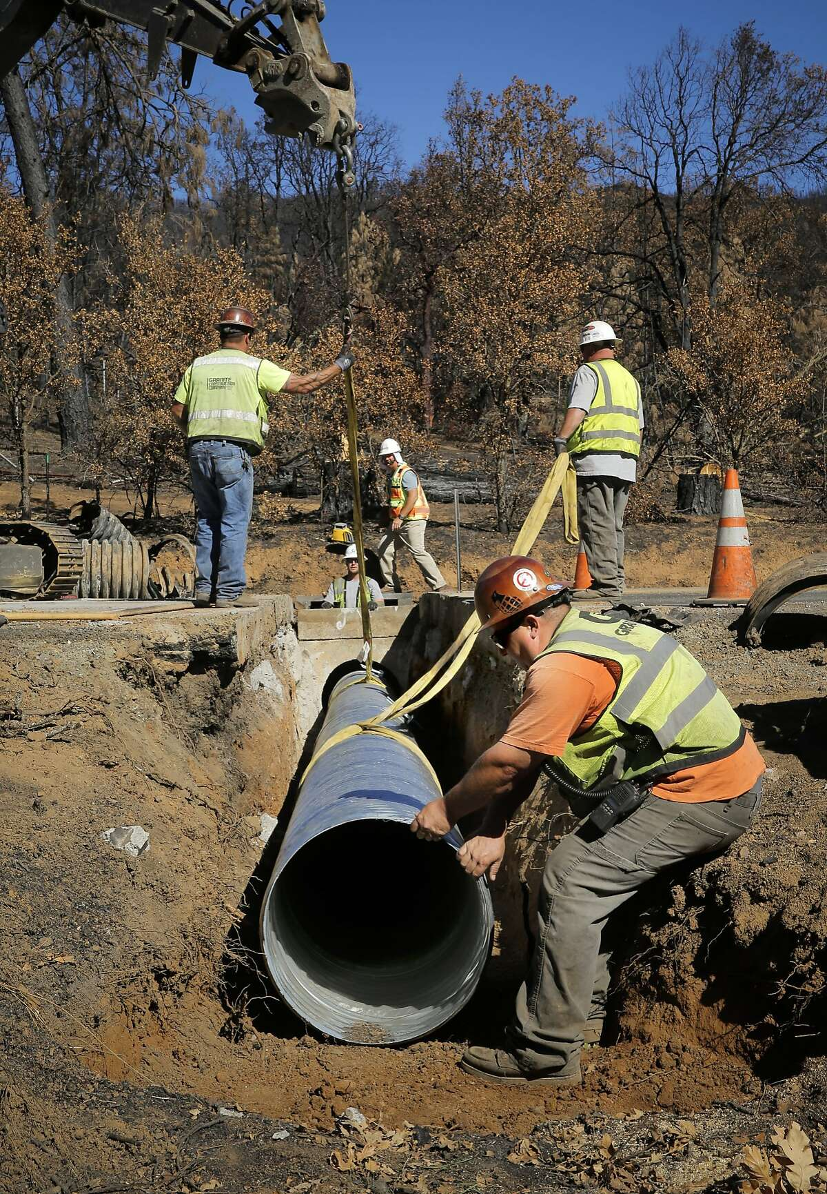 Caltrans contractors including Dustin Pedrotti, (front) replace a fire damaged drainage pipe that runs under highway 175, on Tues. Oct. 20, 2015, in preparation of possible heavy rains this winter after the Valley Fire swept through the highway near Middletown, Calif.