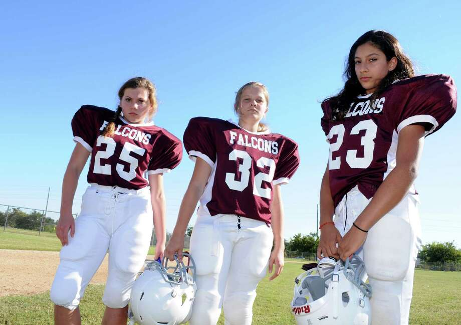 Fort Settlement Middle School Falcons eighth-grade football players Macy Hicks (25), left, Mia Duvenhage (32), and Grace Elias (23) wait for the start of a scrimmage game. / Freelance