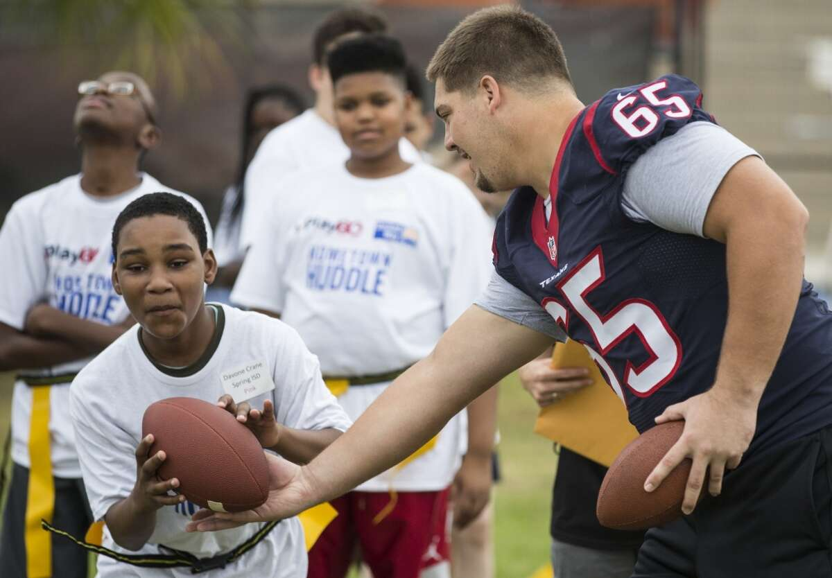 Houston Texans center Greg Mancz (65) hands the football off to Davone Crane during a Houston Texans Hometown Huddle mini camp for Special Olympics athletes on Tuesday, Oct. 20, 2015, in Houston. Texans rookies and head coach Bill O'Brien ran through various football drills with more than 100 Special Olympics athletes, in conjunction with the NFL Play 60 program, at the Houston Texans YMCA. ( Brett Coomer / Houston Chronicle )
