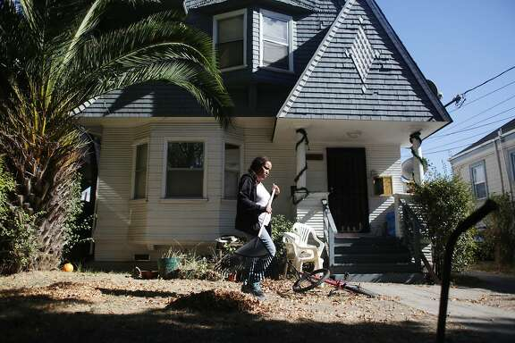 Annette Miller, rakes leaves in her front yard on Tuesday, October 21,  2015 in Oakland, Calif.