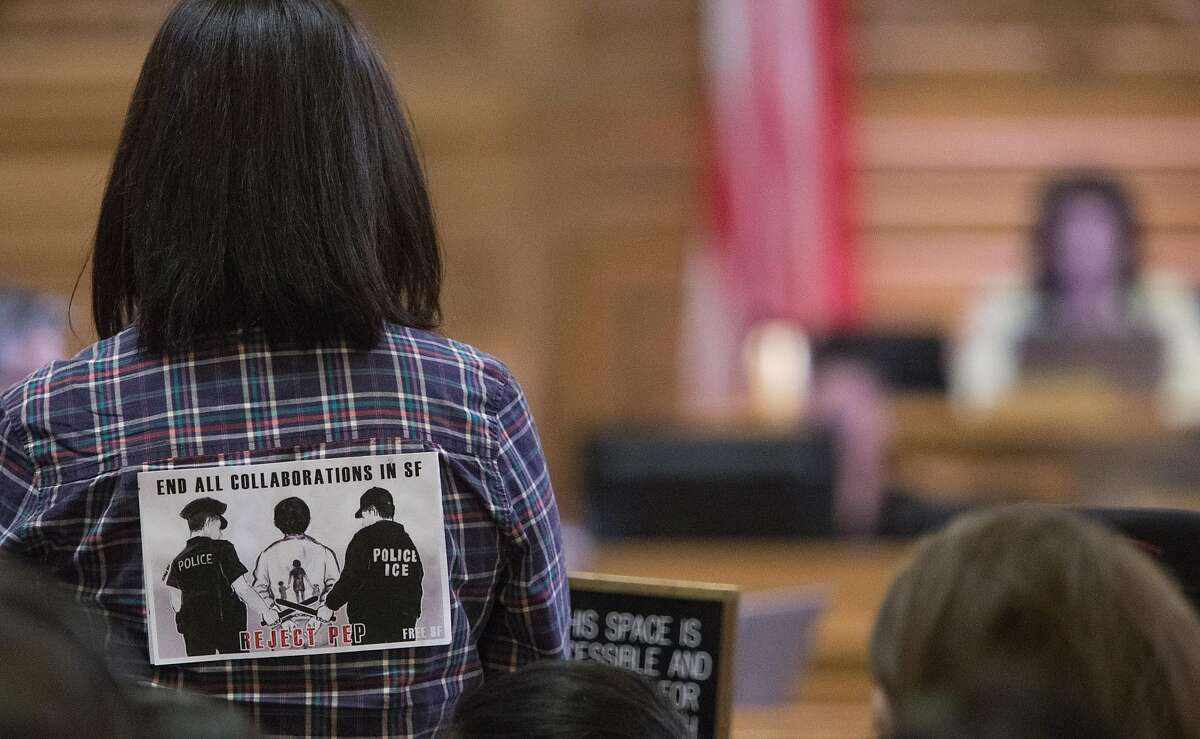 Yadira Sanchez, whose father was mistakenly deported, stands while her story is told in front of the Board of Supervisors at City Hall on Tuesday, Oct. 20, 2015 in San Francisco, Calif.