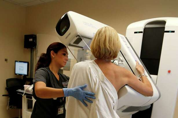 Andrea Quinn, a nine-year survivor of ovarian cancer gets a routine mammagram screen by technologist Joanna Esquivel at the Mays Clinic at MD Anderson on Tuesday, Oct. 20, 2015, in Houston.  The American Cancer Society, which has for years taken the most aggressive approach to screening, issued new guidelines on Tuesday, recommending that women with an average risk of breast cancer start having mammograms at 45 and continue once a year until 54, then every other year for as long as they are healthy and expected to live another 10 years. One of the most respected and influential groups in the continuing breast-cancer screening debate said on Tuesday that women should begin mammograms later and have them less frequently than it had long advocated. ( Karen Warren / Houston Chronicle )