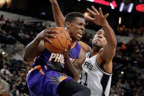 Phoenix Suns guard Eric Bledsoe, left, is defended by San Antonio Spurs forward Tim Duncan during the first half of a preseason NBA basketball game, Tuesday, Oct. 20, 2015, in San Antonio. (AP Photo/Darren Abate)