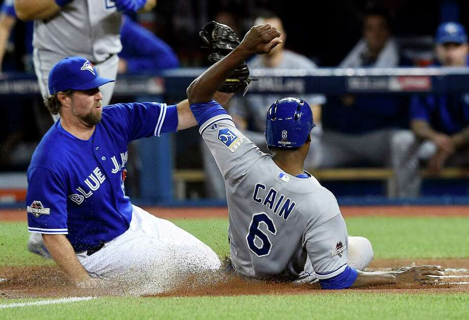 Lorenzo Cain beats the tag by R.A. Dickey to score on a passed ball in the Royals' four-run first inning. Photo: Shane Keyser, MBR / Kansas City Star
