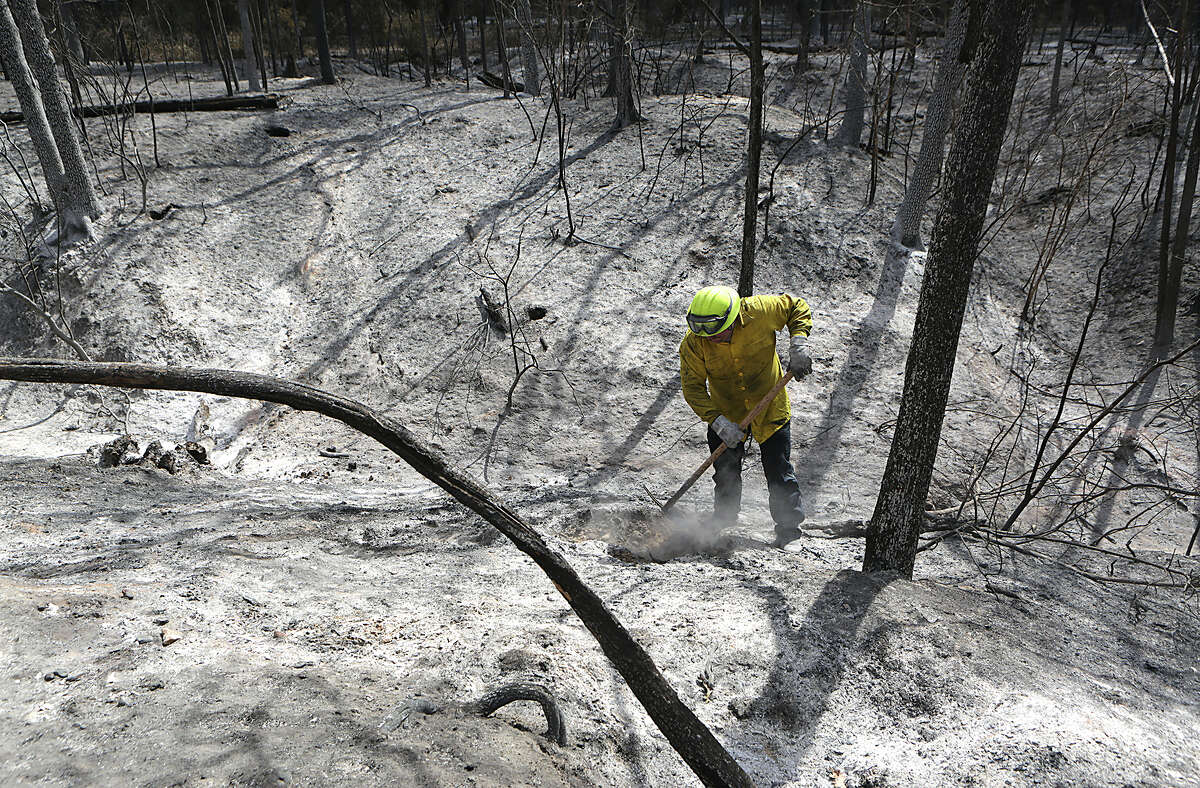 A firefighter breaks up a smoldering tree stump in the badlly burned area of the Hidden Pines Fire. Residents were allowed to return to their homes in the burned areas of the Hidden Pines Fire on Tuesday, October 20, 2015, between Smithville and Bastrop, TX.