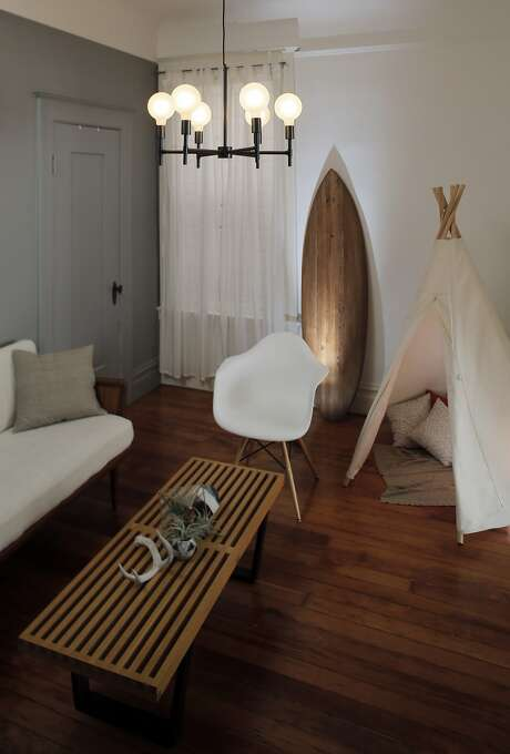 The sitting room with wooden surfboard and child-size teepee in the home of Jennine Jacob, an advocate of waste-free living, who runs Mrs. Peasy party-ware rentals from her S.F. home. Photo: Carlos Avila Gonzalez, The Chronicle