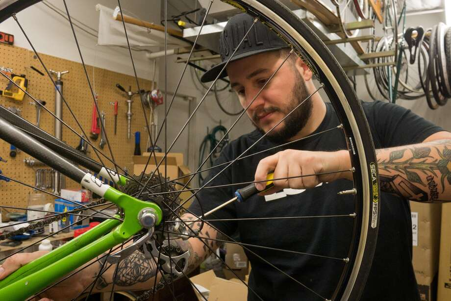 Ham Cycles owner Kasey Dixon works on a bike in his shop, located at 2309 Dunlavy. Dixon uses West  Alabama when he bikes to work.He said the street does not feel safe for cyclists. Photo: R. Clayton McKee, Freelance / © R. Clayton McKee