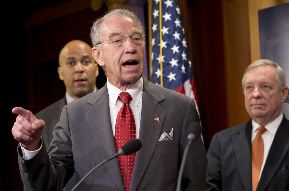 Senate Judiciary Committee Chairman Sen. Charles Grassley, R-Iowa, center, flanked by Sen. Cory Booker, D-N.J., left, and Senate Minority Whip Richard Durbin of Ill., speaks about criminal justice reform, Thursday, Oct. 1, 2015, during a news conference on Capitol Hill in Washington. A long-awaited bipartisan proposal to cut mandatory prison sentences for nonviolent offenders and promote more early release from federal prisons is scheduled to be disclosed Thursday by an influential group of senators who hope to build on backing from conservatives, progressives and the White House. (AP Photo/Jacquelyn Martin) Photo: Jacquelyn Martin, Associated Press