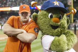 HOUSTON, TX - MARCH 31:  Defensive end J.J. Watt of the Houston Texans poses with Houston Astros mascot Orbit after throwing out the first pitch during opening night at Minute Maid Park as the Texas Rangers played the Houston Astros  on March 31, 2013 in Houston, Texas.  (Photo by Bob Levey/Getty Images)