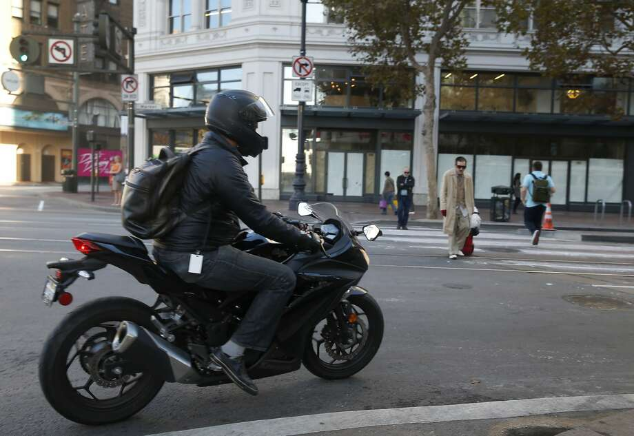 A motorcyclist makes an illegal right turn on Market Street from Sixth Street in San Francisco, Calif. on Wednesday, Oct. 21, 2015. Photo: Paul Chinn, The Chronicle