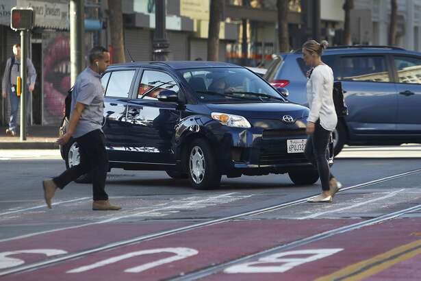 """A driver turns right onto Market Street from northbound Sixth Street despite """"no right turn"""" signs posted at the intersection in San Francisco, Calif. on Wednesday, Oct. 21, 2015."""
