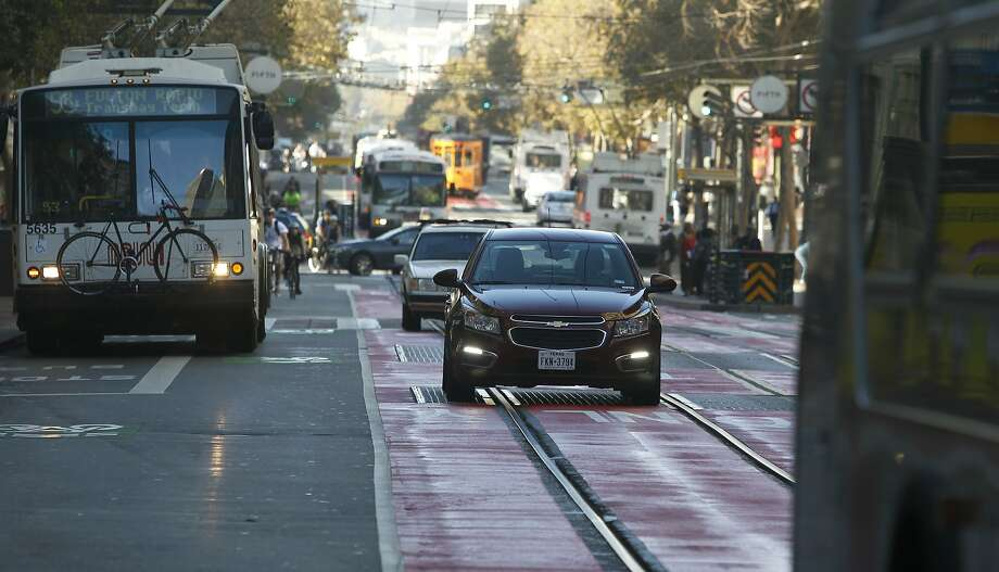 Private cars drive in lanes painted red to indicate they're restricted for use by buses and taxis on Market Street near Fourth. Photo: Paul Chinn, The Chronicle
